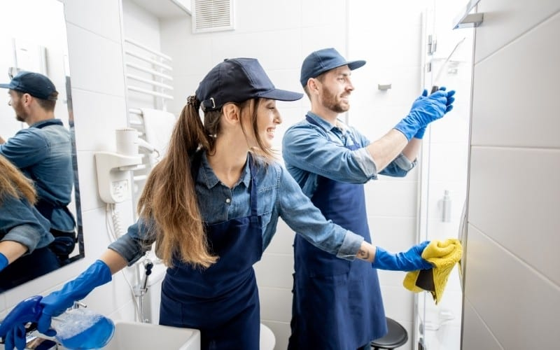 Two people cleaning a bathroom
