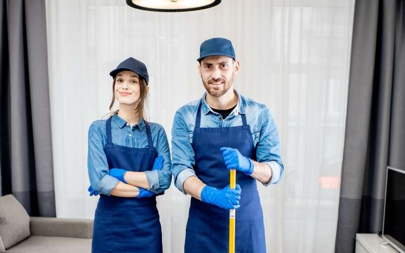 Two people wearing cleaners clothes while holding a broom